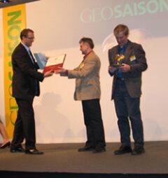"""ITB, Berlin, 13.3.2005: Christoph Kucklick, Chefredakteur der GEO SAISON, überreicht an Arthur Schnabl und Dusan Dohnal (rechts) eine """"Goldene Palme 2005""""."""