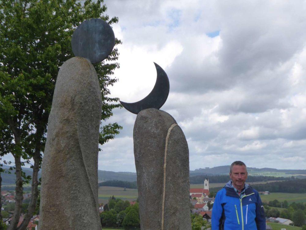Rudi am Kunstwanderweg dahinter die Jakobskirche in Eschlkam